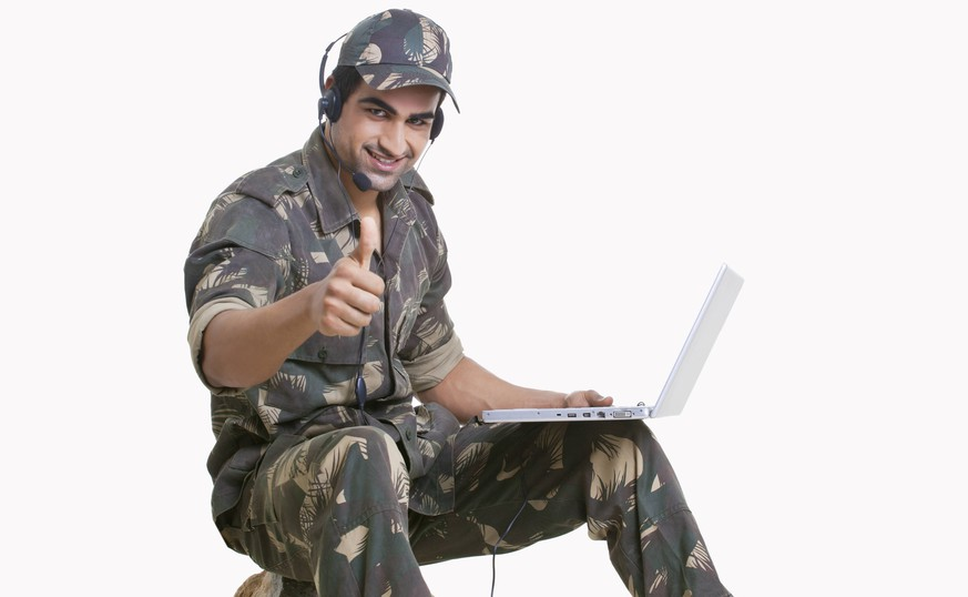 Young soldier using laptop and showing thumbs up sign PUBLICATIONxNOTxINxIND