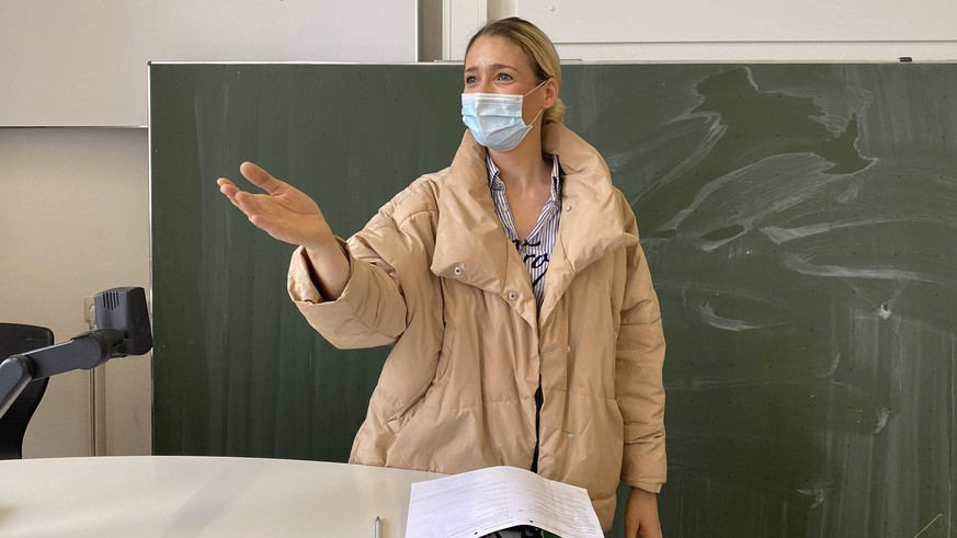 Lehrerin mit dicker Winterjacke und Mundschutzmaske im Präsenzunterricht, Gestik, Corona-Krise, Stuttgart, Baden-Württemberg, Deutschland Coronavirus *** Teacher with thick winter jacket and face mask in classroom teaching, gestures, corona crisis, Stuttgart, Baden Württemberg, Germany Coronavirus