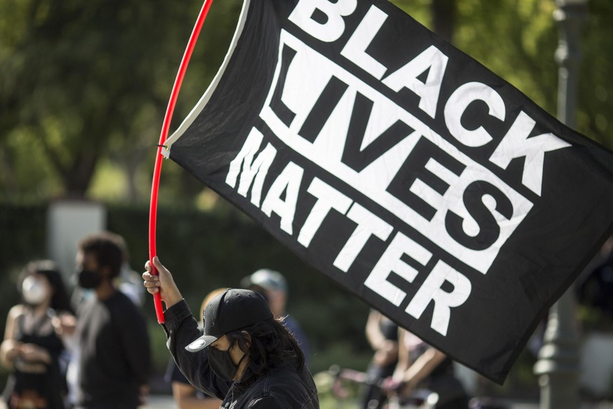 A man holding a BLACK LIVES MATTER flag outside Los Angeles Mayor Garcetti's house after a guilty verdict was announced at the trial of former Minneapolis police Officer Derek Chauvin for the 2020 death of George Floyd, Tuesday, April 20, 2021, in Los Angeles. Former Minneapolis police Officer Derek Chauvin has been convicted of murder and manslaughter in the death of Floyd. (AP Photo/Ringo H.W. Chiu)