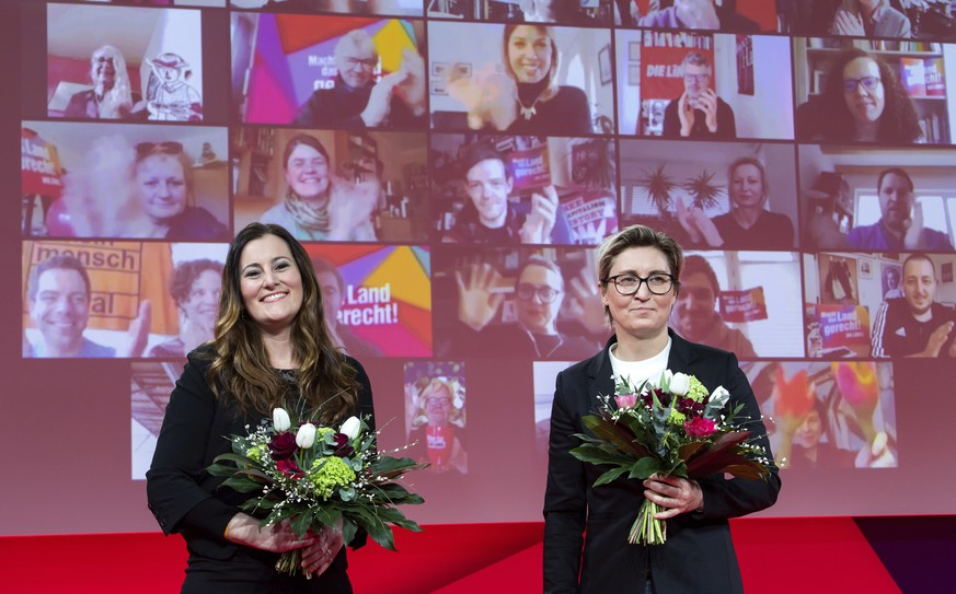 Janine Wissler, left, and Susanne Hennig-Wellsow, the new federal leaders of the Left Party, stand together after their election at the Left Party's online federal party conference, each holding a bouquet of flowers in Berlin, Germany, Saturday, Feb.27, 2021. (Bernd von Jutrczenka/Pool via AP)