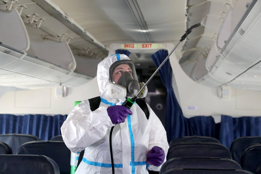 KYIV REGION, UKRAINE - JUNE 13, 2020 - An employee in protective clothing disinfects overhead bins during a demonstration at Boryspil International Airport, Kyiv Region, northern Ukraine. Aircraft disinfection at Boryspil Aiport Copyright: xPavloBagmutx