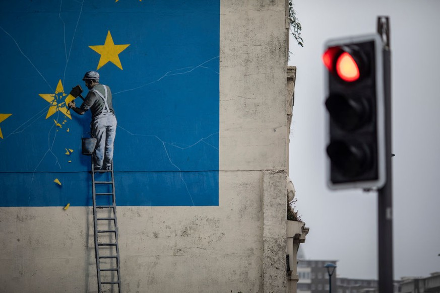 DOVER, ENGLAND - AUGUST 29: A red traffic light in front of a painted mural by British graffiti artist Banksy, depicting a workman chipping away at one of the stars on a European Union (EU) themed flag on August 29, 2018 in Dover, England.  (Photo by Dan Kitwood/Getty Images)
