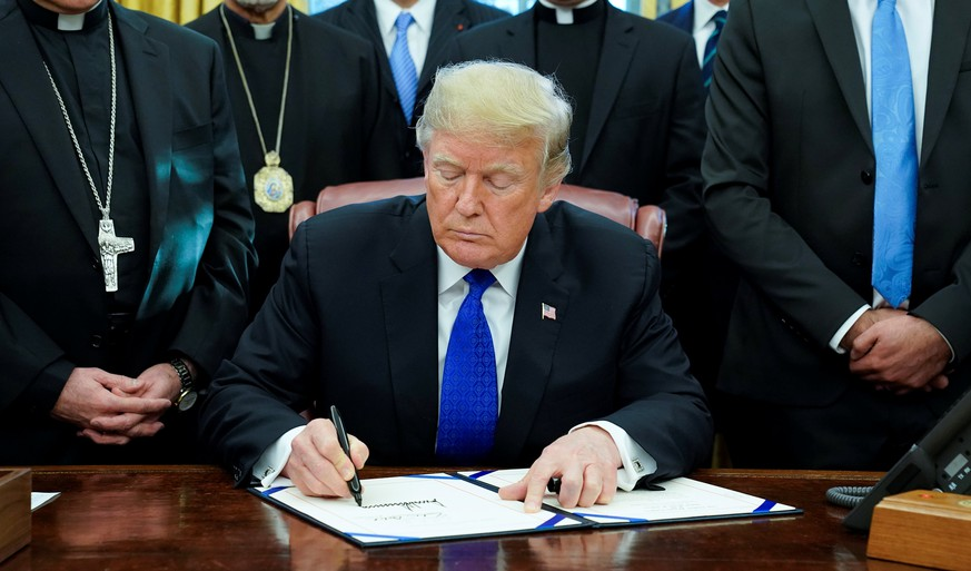 U.S. President Donald Trump signs the Iraq and Syria Genocide Relief and Accountability Act of 2018 in the Oval Office of the White House in Washington, U.S., December 11, 2018.  REUTERS/Jonathan Ernst