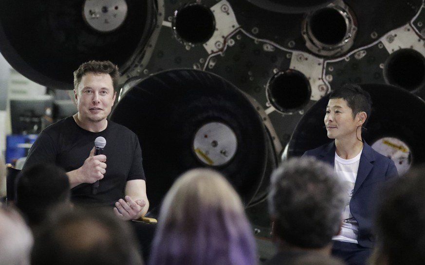 SpaceX founder and chief executive Elon Musk, left, announces Japanese billionaire Yusaku Maezawa, right, as the first private passenger on a trip around the moon, Monday, Sept. 17, 2018, in Hawthorne, Calif. (AP Photo/Chris Carlson)