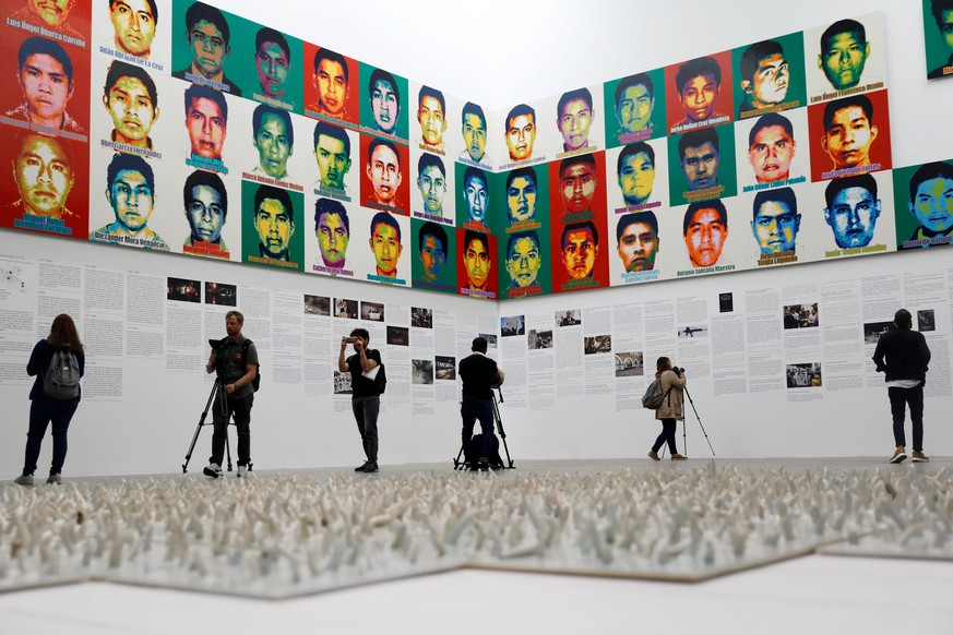 Journalists are seen in front of portraits of the 43 missing Ayotzinapa College Raul Isidro Burgos students during a press preview of the exhibition