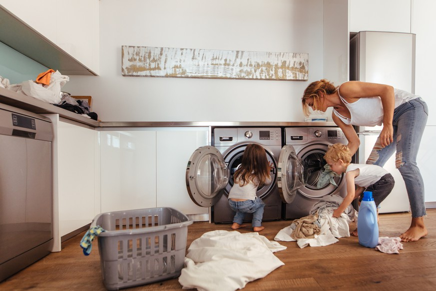 Woman with kids load clothes in washing machine. Mother and children putting laundry into washing machine at home.