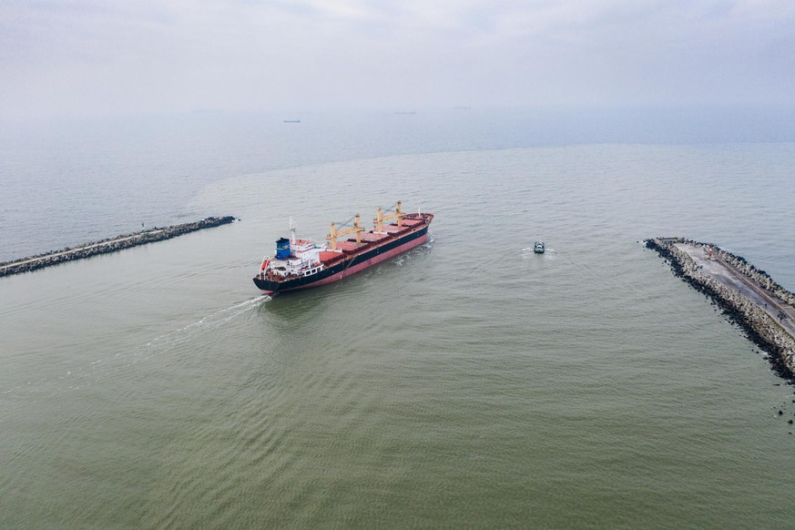 The pilot ship accompanies the cargo vessel at the exit from the shipping channel. Aerial drone shot taken in Kaliningrad region, Russia.