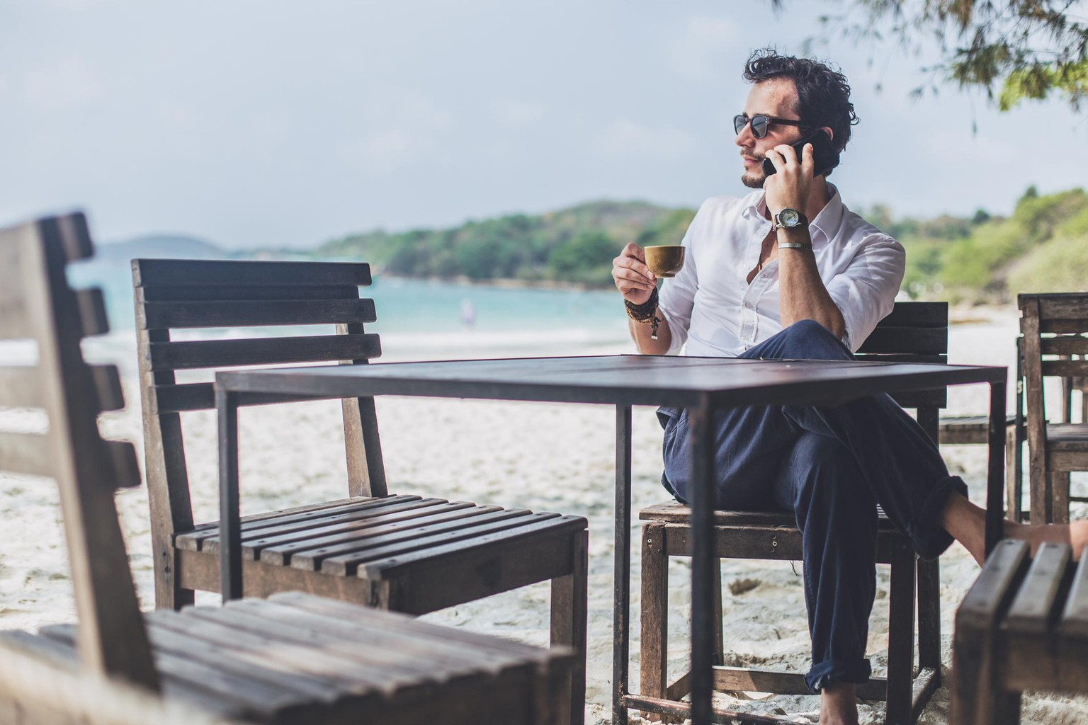 One man, man on the beach, drinking coffee in cafe, talking on mobile phone.