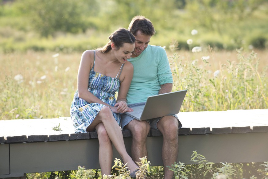 Couple sitting on countryside boardwalk with laptop computer PUBLICATIONxINxGERxSUIxAUTxONLY Copyright: EricxAudras B04659129