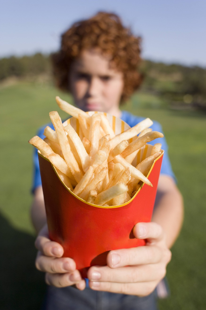 Boy holding chips MODEL RELEASED. Boy holding chips. These are fried chipped potato portions. They are a popular fast food item, but can contain large amounts of unhealthy saturated fats. Potatoes are a good source of carbohydrates such as starch. PUBLICATIONxINxGERxSUIxHUNxONLY IANxHOOTON/SCIENCExPHOTOxLIBRARY F001/2446