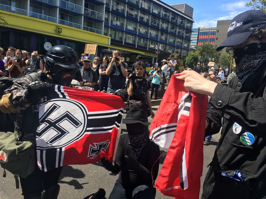 Counter protesters tear a Nazi flag, Saturday, Aug. 4, 2018 in Portland, Ore. Small scuffles broke out Saturday as police in Portland, Oregon, deployed