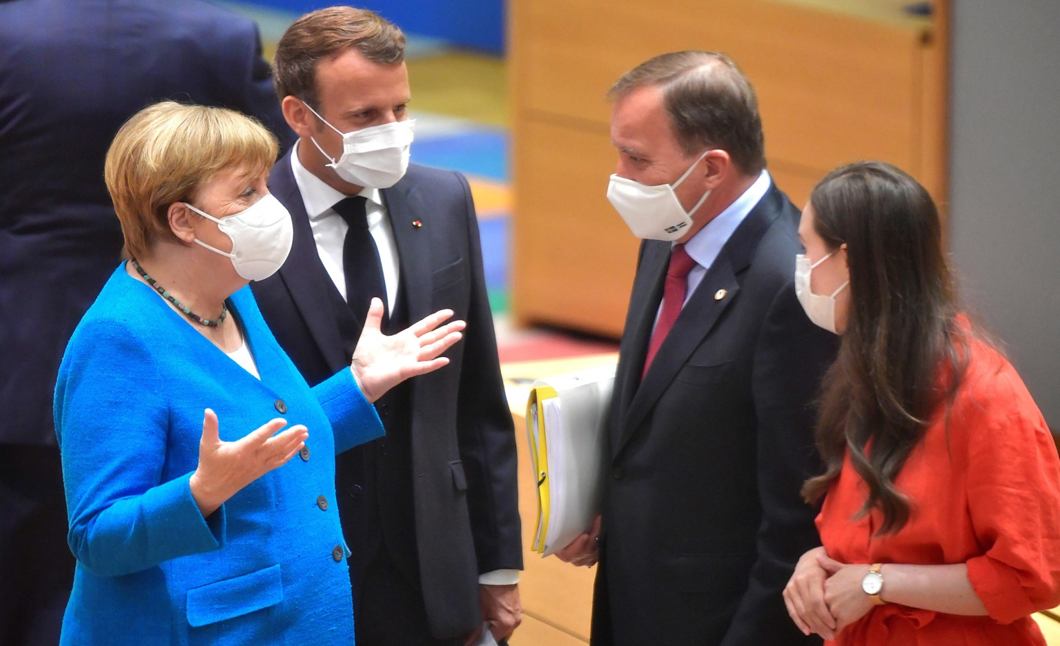 German Chancellor Angela Merkel, left, and French President Emmanuel Macron, second left, speak with Sweden's Prime Minister Stefan Lofven, second right, and Finland's Prime Minister Sanna Marin, right, during a round table meeting at an EU summit in Brussels, Saturday, July 18, 2020. Leaders from 27 European Union nations meet face-to-face for a second day of an EU summit to assess an overall budget and recovery package spread over seven years estimated at some 1.75 trillion to 1.85 trillion euros. (John Thys, Pool Photo via AP)