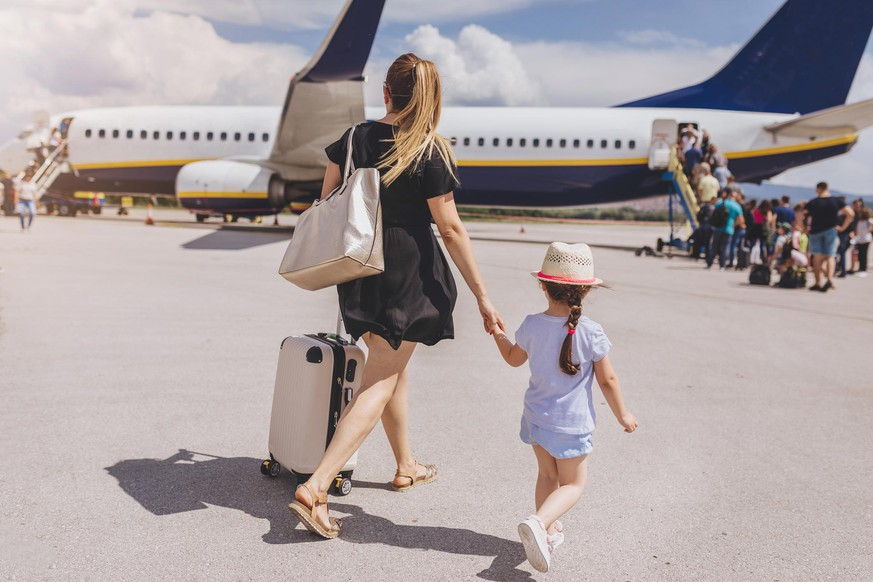 Young mother and her beautiful daughter boarding a plane.
